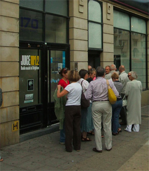 People waiting in line to enter a building.